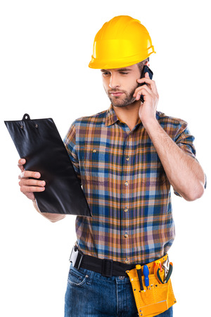 Concentrated on work. Confident young male carpenter in hardhat talking on mobile phone and looking at his clipboard while standing against white background photo