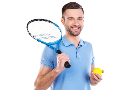 big game: Ready to a big game. Confident young man holding tennis racket and smiling while standing against white background