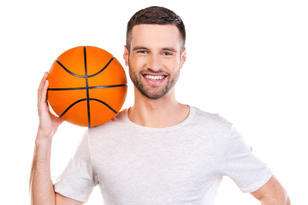 shoulder carrying: Ready to play. Confident young man carrying basketball ball on shoulder and smiling while standing against white background
