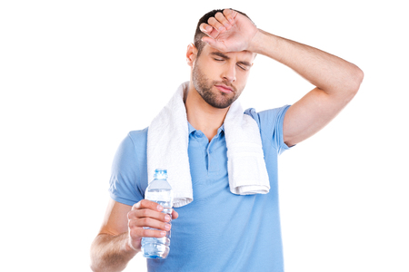 tired: Feeling so tired. Tired young man with towel on shoulders holding bottle with water and smiling while standing against white background Stock Photo