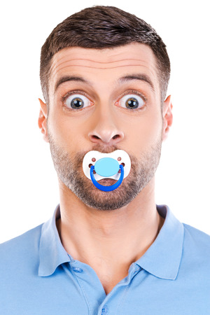 soother: Like a baby. Funny young man with big eyes and pacifier in his mouth staring at camera while standing against white background Stock Photo