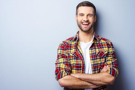 행복 한 젊은 남자. 회색 배경에 서있는 동안 캐주얼 셔츠 유지 팔에 잘 생긴 젊은 남자의 초상화 건너와 미소