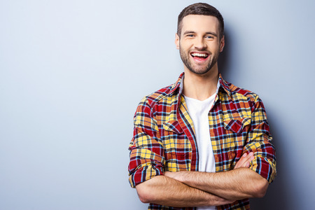 man: Happy young man. Portrait of handsome young man in casual shirt keeping arms crossed and smiling while standing against grey background