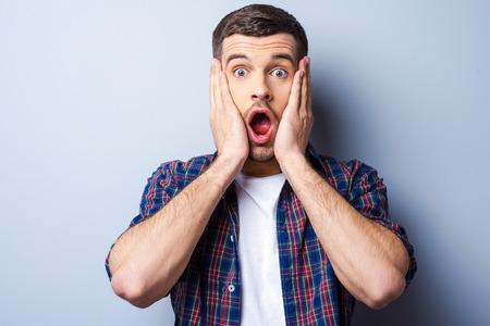 gestos de la cara: Sentirse conmocionado. Hombre joven frustrado en camisa casual mantener la boca abierta y mirando aterrorizado mientras toca su cara y de pie contra el fondo gris Foto de archivo