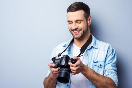 좋은 기회! 디지털 카메라를 들고 회색 배경으로 서있는 동안 미소로 찾고 잘 생긴 젊은 남자
