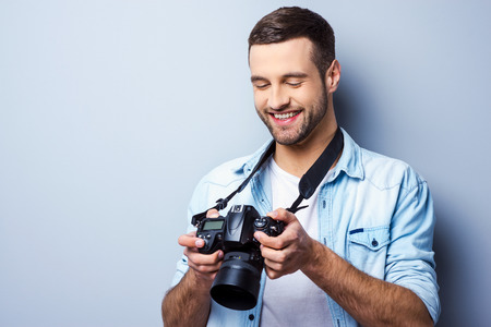 Great shot! Handsome young man holding digital camera and looking at it with smile while standing against grey background Archivio Fotografico