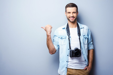 Photographers choosing it. Handsome young man with digital camera pointing away and smiling while standing against grey background