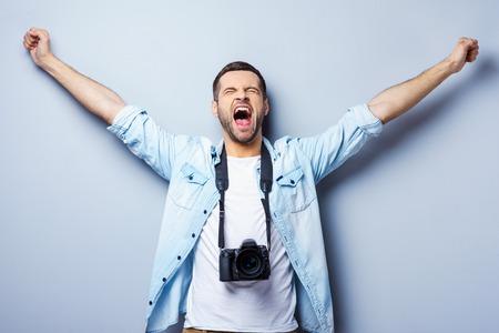 gestos de la cara: Fot�grafa de �xito. Hombre joven feliz con la c�mara digital de mantener los brazos en alto y los ojos cerrados mientras est� de pie contra el fondo gris