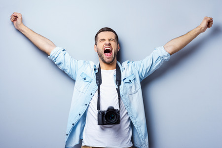 photographer: Successful photographer. Happy young man with digital camera keeping arms raised and eyes closed while standing against grey background