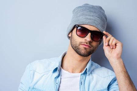 anteojos de sol: Confiados en su estilo perfecto. Hombre de moda joven hermoso que ajusta sus gafas de sol y mirando a la cámara mientras está de pie contra el fondo gris