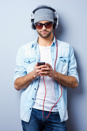 Looking for his favorite song. Handsome young stylish man in headphones holding MP3 Player and looking at it while standing against grey background