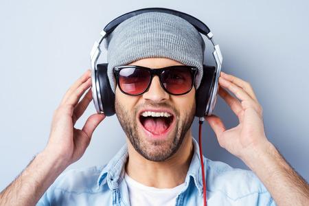 gestos de la cara: Disfrutando de su canci�n favorita. Hombre con estilo joven feliz en auriculares que expresan positividad y mirando a la c�mara mientras est� de pie contra el fondo gris