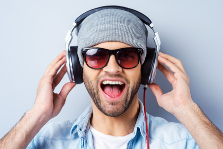 expression: Enjoying his favorite song. Happy young stylish man in headphones expressing positivity and looking at camera while standing against grey background Stock Photo