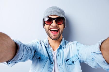 저와 또 다른 사람 그냥. 회색 배경에 서있는 동안 모자에 잘 생긴 젊은 남자의보기와는 셀프 카메라를 만들고 미소 선글라스