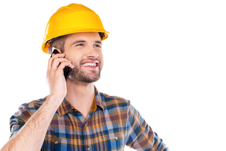 Happy with work done. Happy young male carpenter in hardhat talking on mobile phone and smiling while standing against white background photo