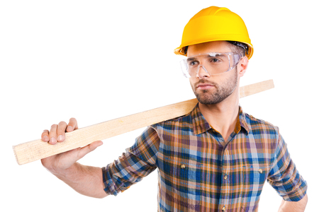 protective eyewear: Confident contractor. Confident young male carpenter in hardhat and protective eyewear carrying wooden balk on shoulder while standing against white background
