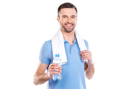 standing water: Staying hydrated. Confident young man with towel on shoulders holding bottle with water and smiling while standing against white background Stock Photo