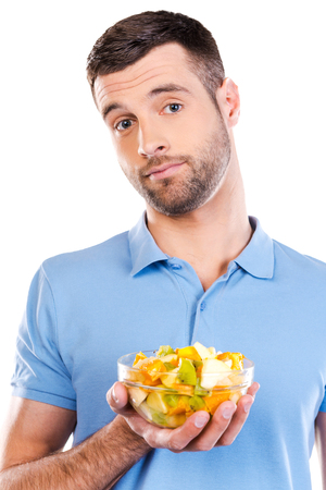 uncertain: Salad again? Frustrated young man holding bowl with fruit salad and looking uncertain while standing against white background