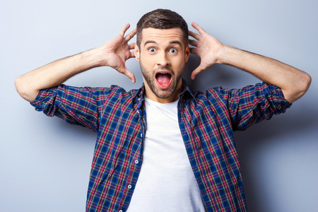 This is amazing! Surprised young man in casual shirt keeping mouth open and staring at camera while standing against grey background Foto de archivo