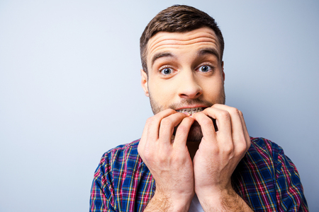 relaxation background: Terrified with something. Frustrated young man in casual shirt keeping mouth open and looking terrified while standing against grey background Stock Photo