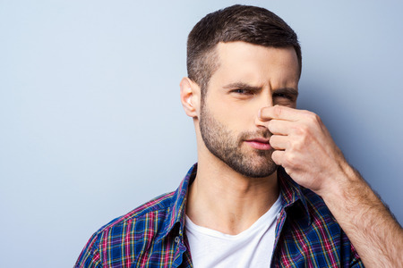 unpleasant smell: Disgusting smell. Portrait of frustrated young man in casual shirt holding nose and expressing negativity while standing against grey background