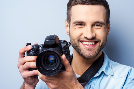 human photography: Smile to a camera! Handsome young man holding digital camera and smiling while standing against grey background