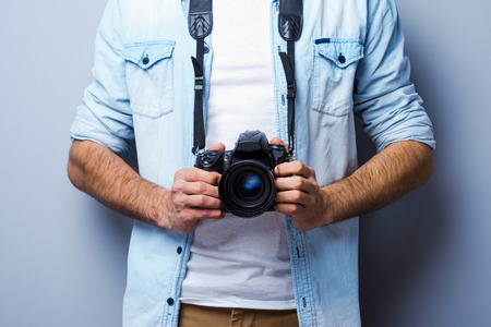 photography themes: Man with digital camera. Cropped image of man with digital camera standing against grey background Stock Photo