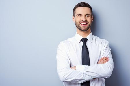 hombre de negocios: Joven y exitoso. Retrato de hombre joven y guapo en camisa y corbata mantener los brazos cruzados y sonriendo mientras est� de pie contra el fondo gris