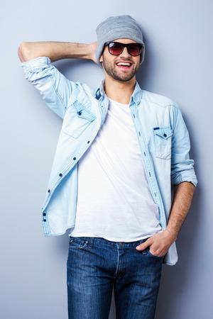 Jong en cool. Knappe jonge stijlvolle man in zonnebril en hoed op zoek naar de camera en glimlachen terwijl staande tegen de grijze achtergrond