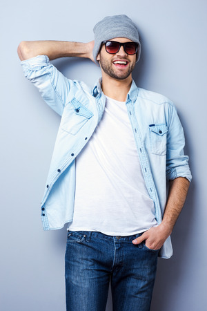 Young and cool. Handsome young stylish man in sunglasses and hat looking at camera and smiling while standing against grey background