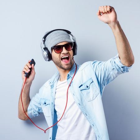 escuchando musica: Dance! Hombre joven con estilo hermoso en auriculares con reproductor de mp3 y el baile de pie sobre fondo gris
