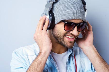 gestos de la cara: Disfrutar de su m�sica favorita. Hombre con estilo joven feliz en el sombrero y gafas de sol que ajusta su anuncio auriculares sonriendo mientras est� de pie contra el fondo gris