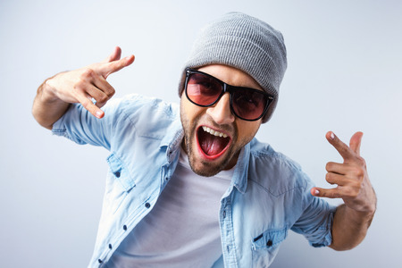 expression: Cool and funky. Top view of handsome young man in hat and sunglasses gesturing and grimacing while standing against grey background Stock Photo