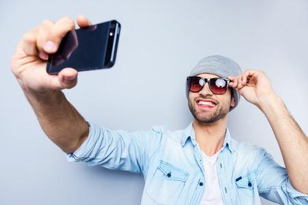 gestos de la cara: Autofoto! Vista superior de hombre joven y guapo en el sombrero y gafas de sol haciendo Autofoto y sonriendo mientras est� de pie contra el fondo gris