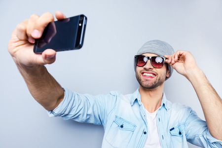 Selfie! Top view of handsome young man in hat and sunglasses making selfie and smiling while standing against grey background
