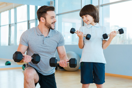 health club: Exercising together. Happy father and son exercising with dumbbells and smiling while standing in health club Stock Photo