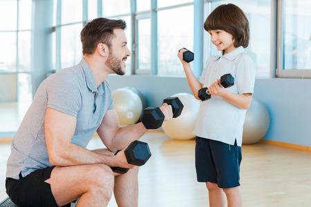 hombres haciendo ejercicio: Hacer ejercicio juntos es divertido. Padre e hijo feliz que ejercita con pesas y sonriendo mientras tanto de pie en el centro de salud Foto de archivo