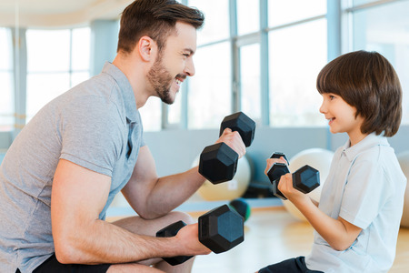 Exercising is fun. Happy father and son exercising with dumbbells and smiling while both standing in health club