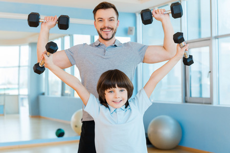 As strong as my father. Happy father and son exercising with dumbbells and looking at camera while both standing in health club photo