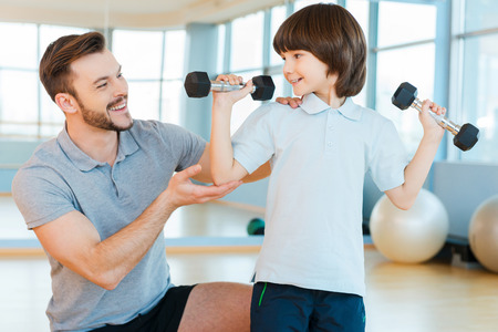 Willing to be strong and healthy. Happy father helping his sun with weight exercises while both standing in health club photo