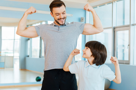 Strong and healthy. Happy father and son showing their biceps and smiling while both standing in health club photo