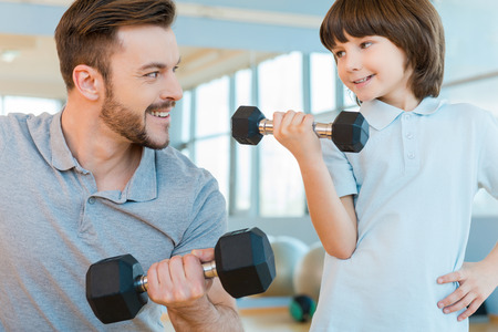 Feeling proud of his son. Happy father and son exercising with dumbbells and smiling while standing in health club together photo