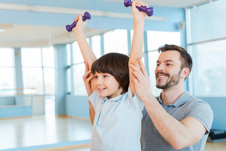 Exercising with fun. Happy father supporting his son in weight training while both standing in health club photo