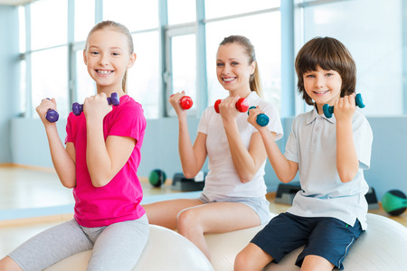 health club: Keeping our bodies fit. Cheerful mother and two children exercising with dumbbells in health club while sitting on the fitness balls together Stock Photo