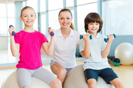 educacion fisica: Instructor con los niños. Instructor Alegre ayudar a los niños con el ejercicio en el club de la salud
