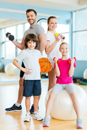 family with two children: Sporty family. Happy family holding different sports equipment while standing close to each other in health club