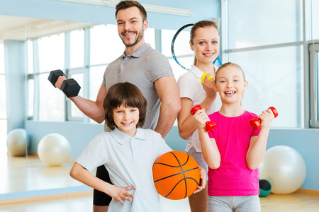 sport training: Happy and sporty. Happy family holding different sports equipment while standing close to each other in health club