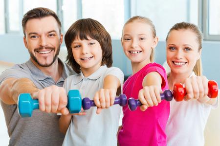 Zdrowego trybu życia razem. Szczęśliwa rodzina trzymając sprzęt różnych dyscyplin sportowych, stojąc blisko siebie w klubie fitness
