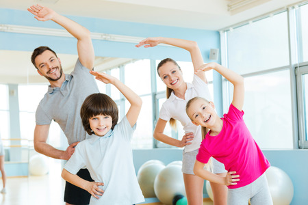 Family exercising. Happy sporty family doing stretching exercises in sports club