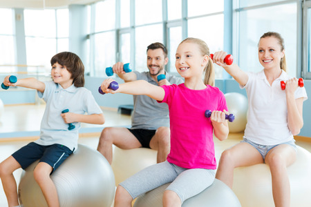 family with two children: Exercising together is fun. Happy sporty family exercising in sports club together Stock Photo